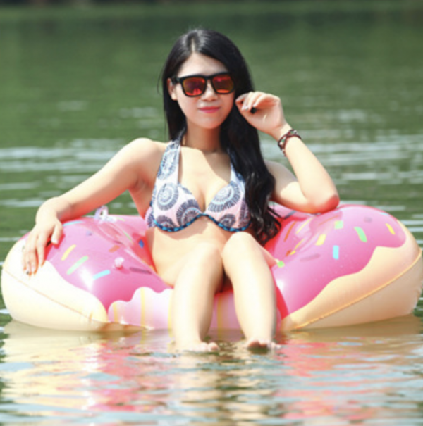 woman in lake floating on donut pool float
